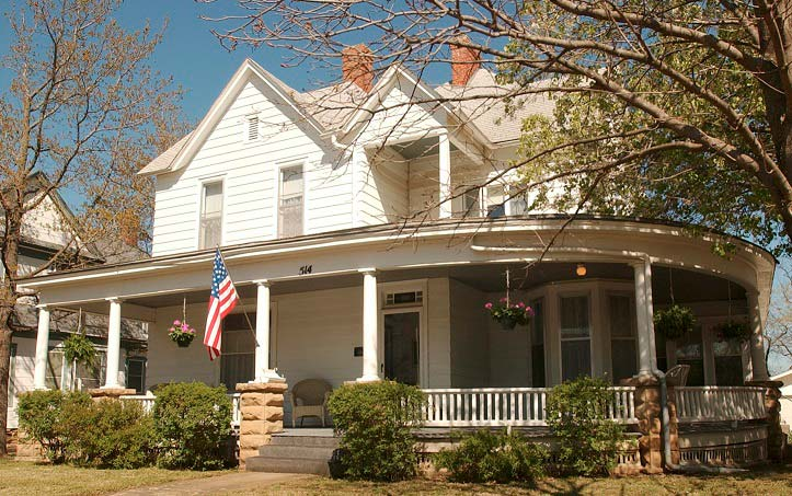 Photo of WIlliam Inge's boyhood home; it is a white house with large, wrap-around porch.